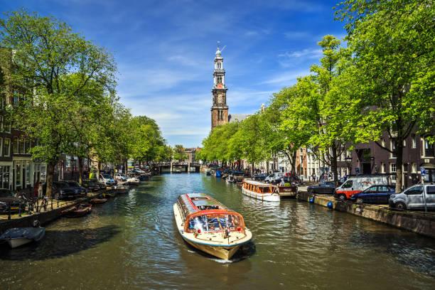 gracht met boot in amsterdam - westerkerk stockfoto's en -beelden