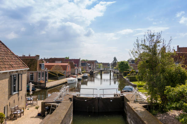 A canal with lock in a historical city in the lake side district of the Netherlands. stock photo