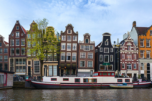 Facades of historic buildings of Amsterdam overlooking the canal, Netherlands.