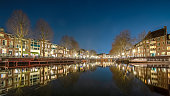 The famous canals in Utrecht, photographed in the evening. The street lighting and the lamps in the houses reflect in the water. Due to the use of slow shutter speed, the water seems as smooth as a mirror