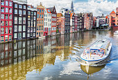 Colorful houses, canal and a classical tour boat of Amsterdam