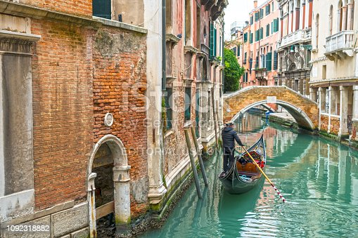 Venice, Italy - February 6, 2018: One gondola sailing in the Venice canal.