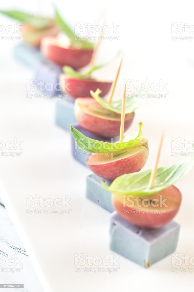 Canape with lavender cheese, grapes and basil royalty-free stock photo