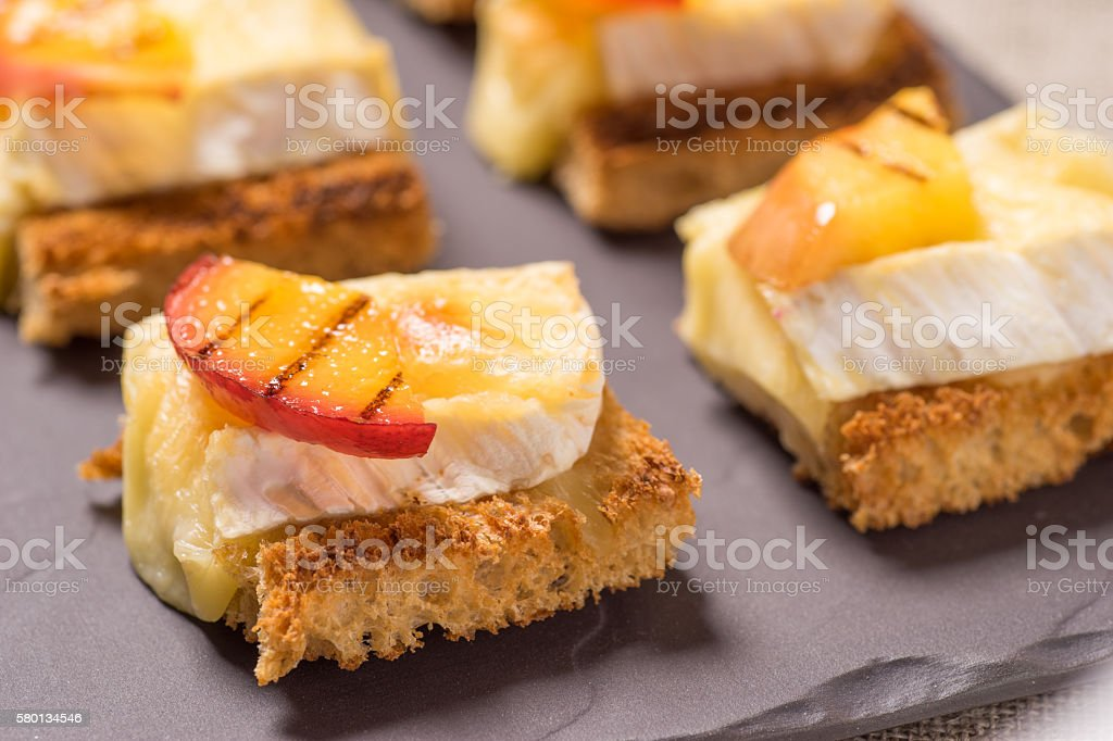 canapes, Appetizer with grilled brie stock photo