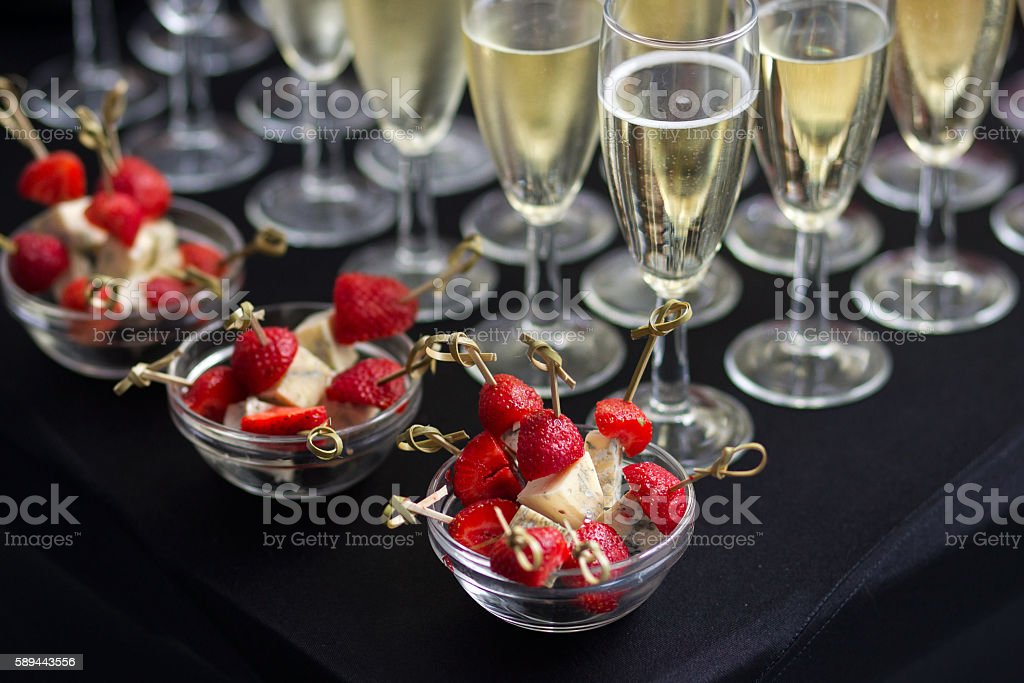Canapes of cheese and strawberries with champagne stock photo