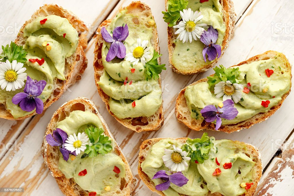 Canapes with avocado paste and edible flowers stock photo