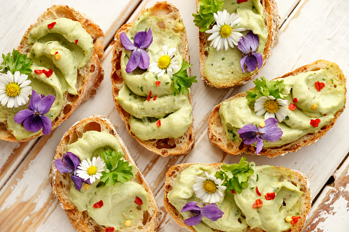 Canapes With Avocado Paste And Edible Flowers Foto de stock y más banco de imágenes de Aguacate