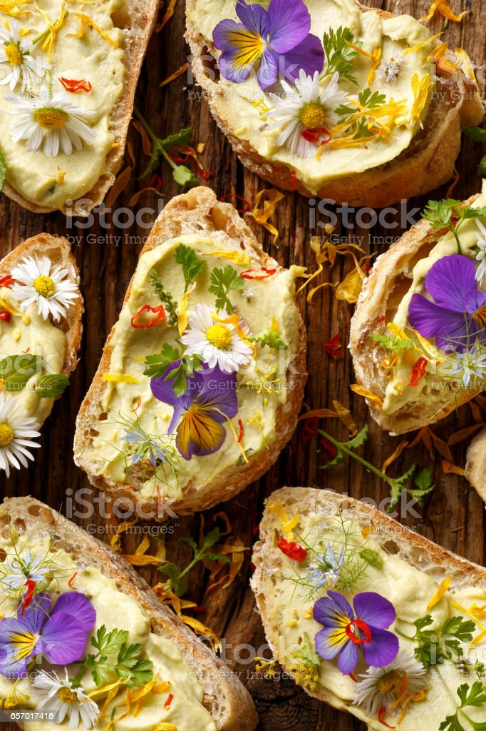 Canapes with eddible flowers and broad bean hummus stock photo