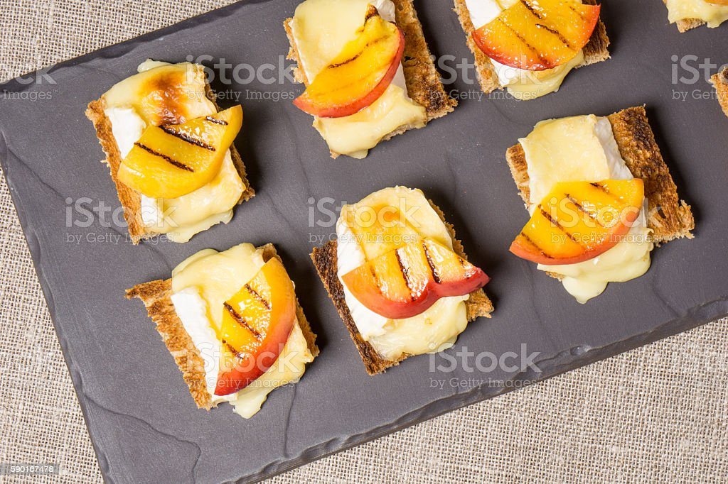 canapes with grilled brie and nectarine stock photo