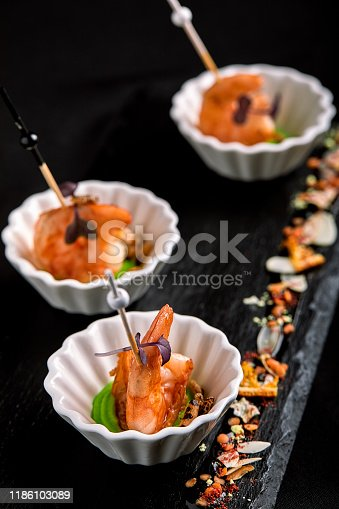 Canapes with tiger prawns on a skewer on a black background. The concept of catering food