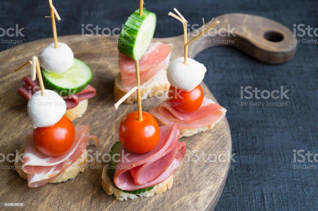 Canapés mit Schinken und Tomaten auf Holzbrett – Foto