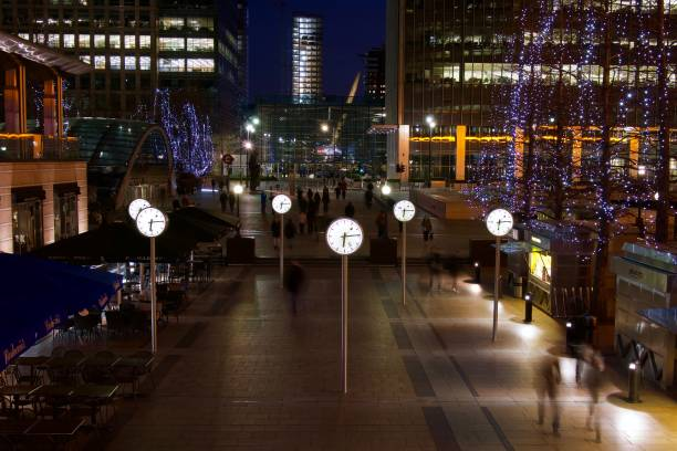 Canary Wharf clocks at night Looking towards the Canary Wharf clocks, in London's Docklands area at night. With long exposure blurred people. skeable stock pictures, royalty-free photos & images