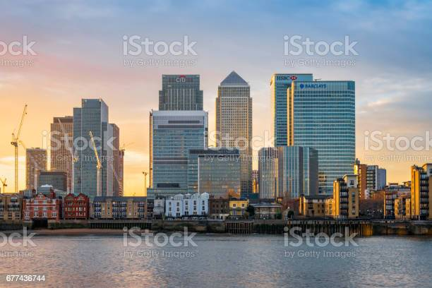 London, United Kingdom - December 22, 2016: View across river Thames to skyscrapers district Canary Wharf in London at sunset. Copy space in sky.