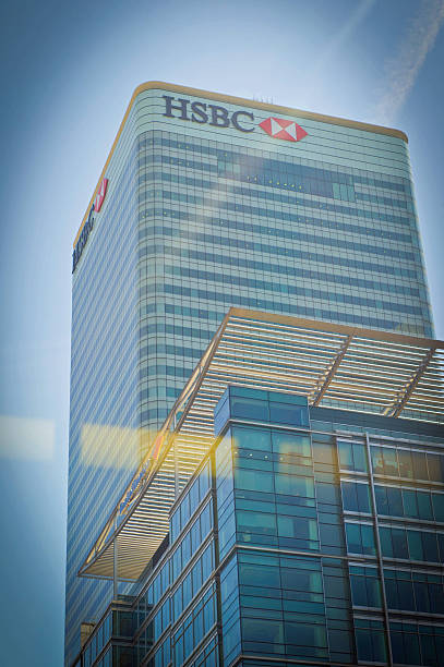 Canary Wharf tower block London, UK - June 11, 2015: Glass skyscraper in Canary Wharf  it shows the HSBC building with reflections on the glass through which the shot is taken. hsbc stock pictures, royalty-free photos & images