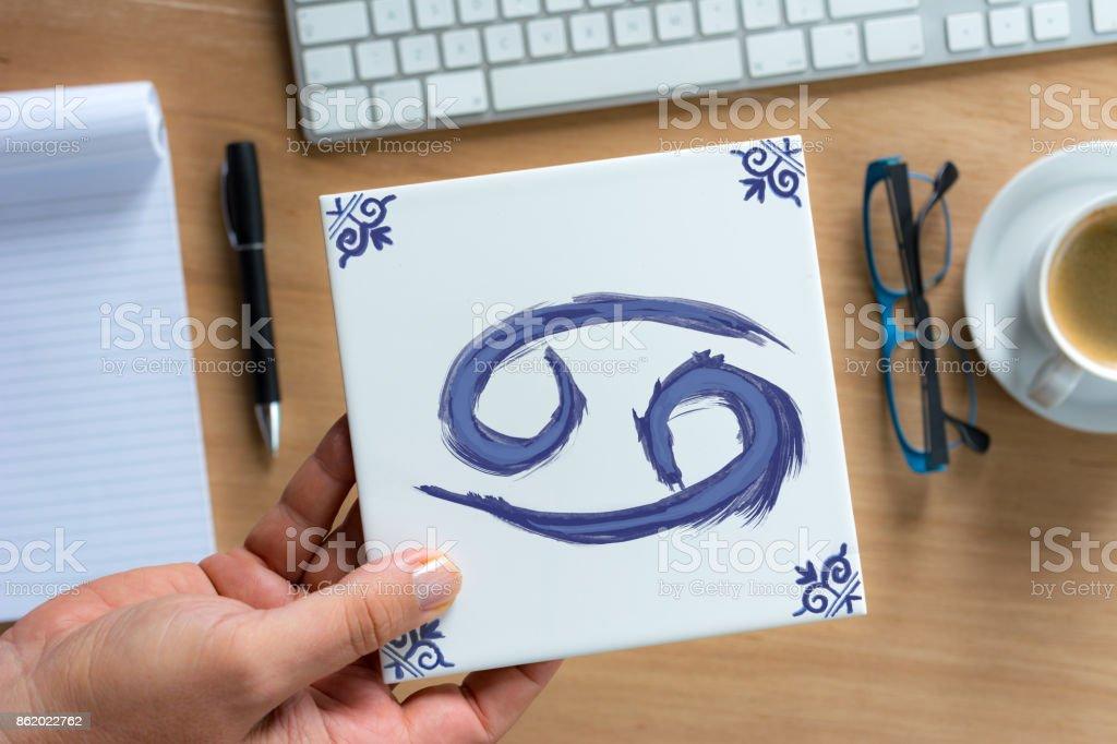 cancer  Delfts Blue zodiac tile above working desk stock photo