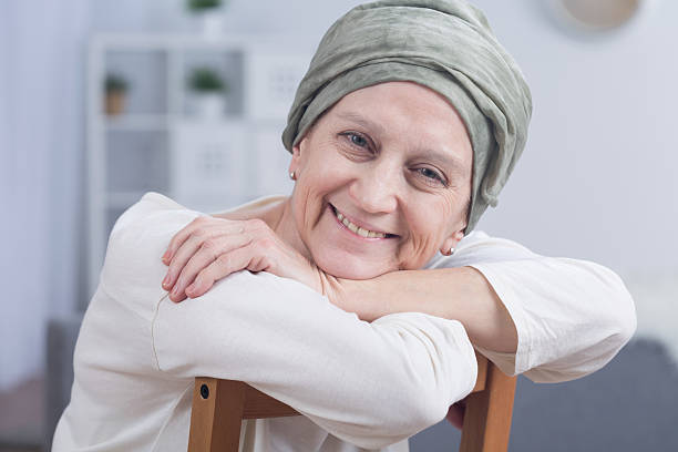 Cancer is not a sentence Cancer woman with headscarf sitting on chair, smiling chemotherapy cancer stock pictures, royalty-free photos & images
