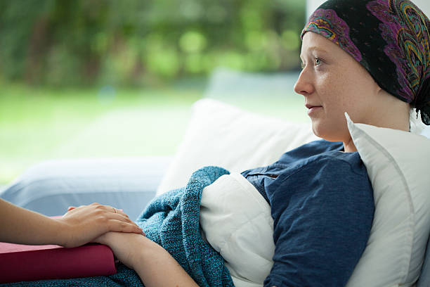 Cancer woman Cancer woman lying in bed supported by mum chemotherapy cancer stock pictures, royalty-free photos & images