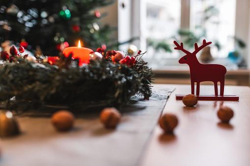 illuminated advent wreath burning in front of festive christmas tree