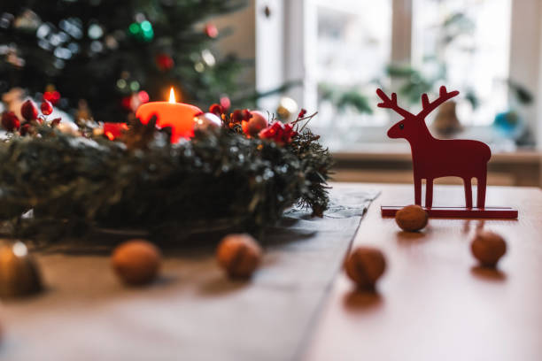 candel of advent wreath burning in front of festive christmas tree stock photo