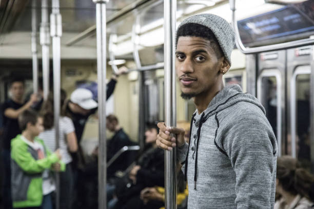 a candid, black man rides a crowded nyc subway train - riding stock photos and pictures