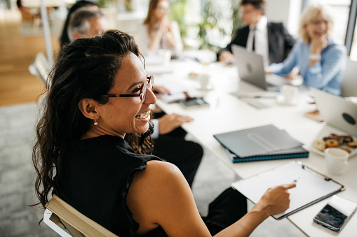 Over the shoulder profile of bespectacled female executive in early 30s sitting at conference table and laughing as she interacts with off-camera colleague.