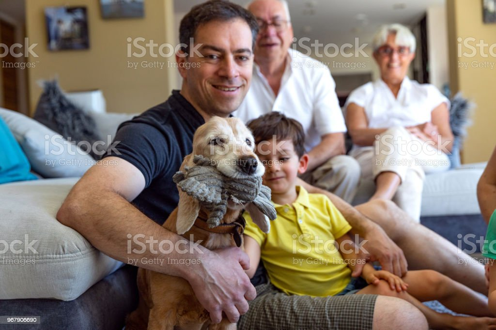 Candid family lifetime during summer holidays at home in the living room with parents and relatives stock photo