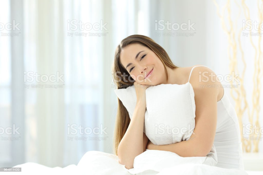 Candid girl holding a pillow and looking at you on a bed royalty-free stock photo