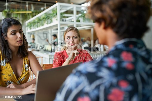1031394390 istock photo Candid group lifestyle shot of three trendy mixed race millennial coworkers meeting together on laptop computer in bright hipster restaurant 1165346272