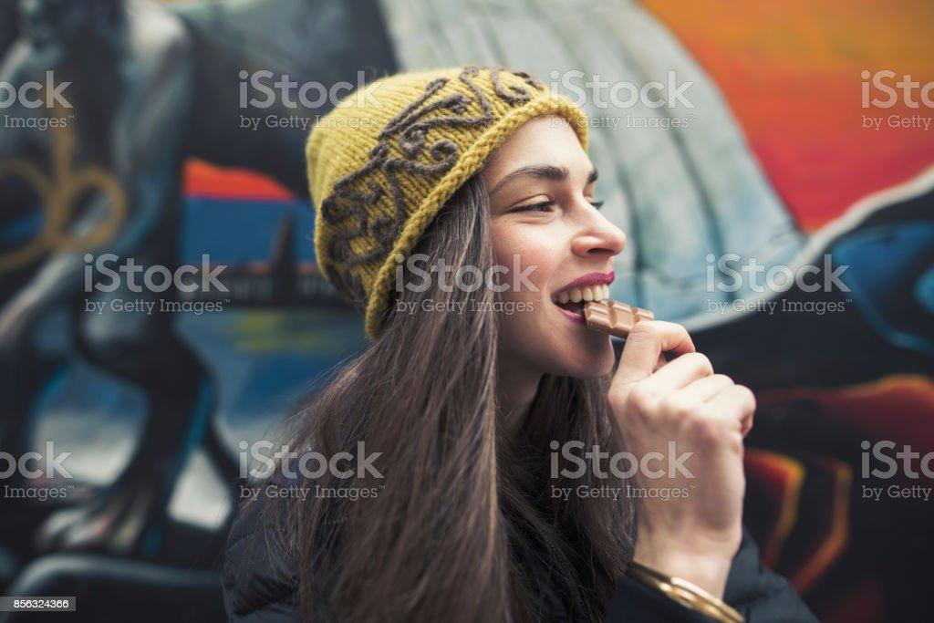 Cândido imagem de uma bela jovem que morder uma barra de chocolate - foto de acervo