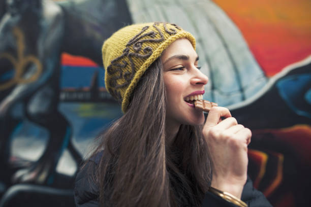 candid image of a beautiful young woman biting a chocolate bar stock photo