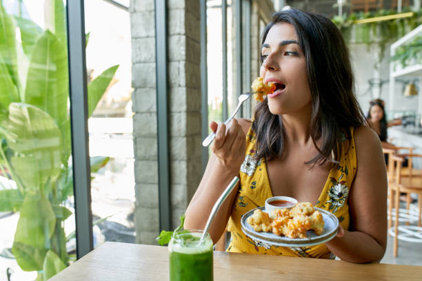 Candid lifestyle portrait of fashionable healthy ethnic businesswoman eating an organic vegetarian cauliflower dish for vegans and drinking green smoothie stock photo