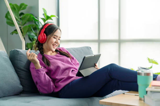 Candid of asian woman using tablet for watching online movie stream mobile device on sofa at living room. Young happy girl enjoying with entertainment media online on weekend. stock photo