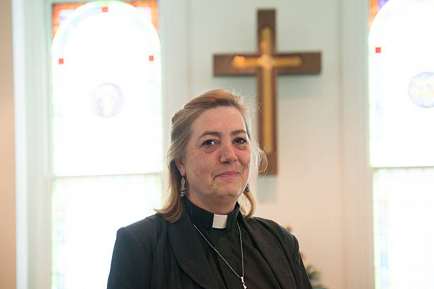 Candid of Female Minister Inside Church Candid of real female pastor inside church with cross in background. clergy stock pictures, royalty-free photos & images