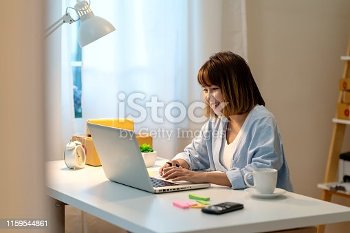 istock Candid of happy young attractive asian woman work at home in evening or late night with SME business owner, young entrepreneur or freelance concept. Young asian student study online in self education. 1159544861