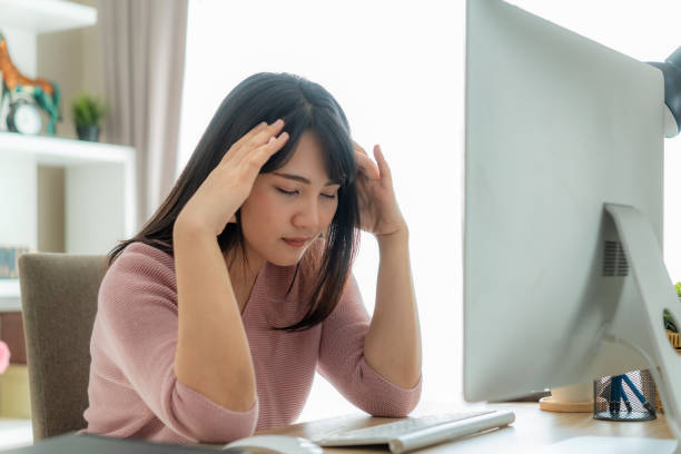 Candid of young Asian single business woman stress out with project business plan on computer laptop or notebook at home office. Concepto del síndrome de agotamiento ocupacional de las personas asiáticas. - foto de stock