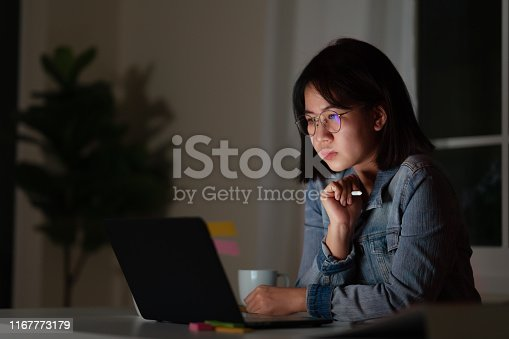istock Candid of young attractive asian female student sitting on desk with smart digital gadget looking at notebook working at late night with project research, graphic designer or programmer concept. 1167773179