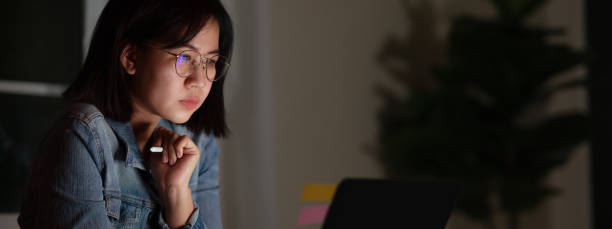 Candid of young attractive asian female student sitting on desk with smart digital gadget looking at notebook working at late night with project research, graphic designer or programmer concept. stock photo