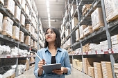 istock Candid of young attractive asian woman auditor or trainee staff work looking up stocktaking inventory in warehouse store by computer tablet with wide angle view. Asian owner or small business concept. 1133945516