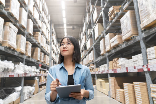 candid of young attractive asian woman auditor or trainee staff work looking up stocktaking inventory in warehouse store by computer tablet with wide angle view. asian owner or small business concept. - warehouse zdjęcia i obrazy z banku zdjęć
