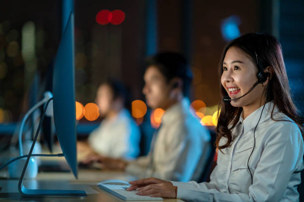 candid of young happy asian woman call centre sitting in office at night shift overtime in concept telesale, teleservice, telemarketing, coronavirus information center, bank or airline representative - shifts call centre foto e immagini stock
