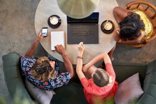 Candid overhead shot of three multi-ethnic millennial coworkers collaborating over coffee with laptop computer at bright cafe serving fair-trade coffee stock photo
