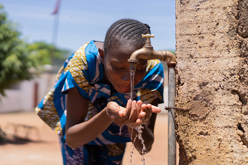 Candid picture of African Black Girl Drinking Water Bamako Mali. Candid Picture of African children drinking and playing with water in Bamako, Mali.