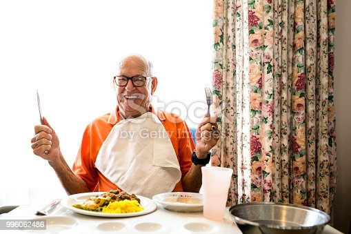 Portrait photo of a happy senior man in his 90ties eating lunch