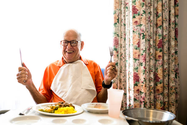 Candid portrait of a happy senior man in his 90ties ready to eat lunch holding up his knife and fork stock photo