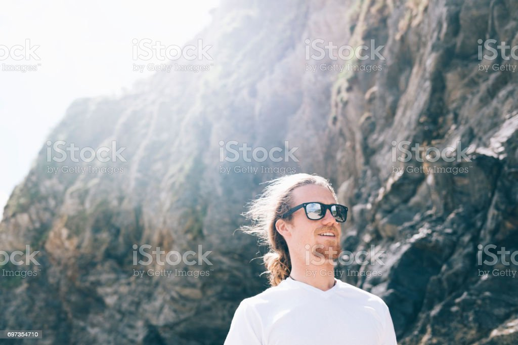 Candid Portrait of a Man in sunglasses on Towan Beach, Newquay. stock photo