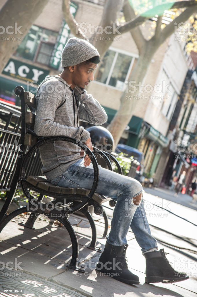 A candid portrait of a young, black man in his twenties waiting on a park bench in New York City stock photo