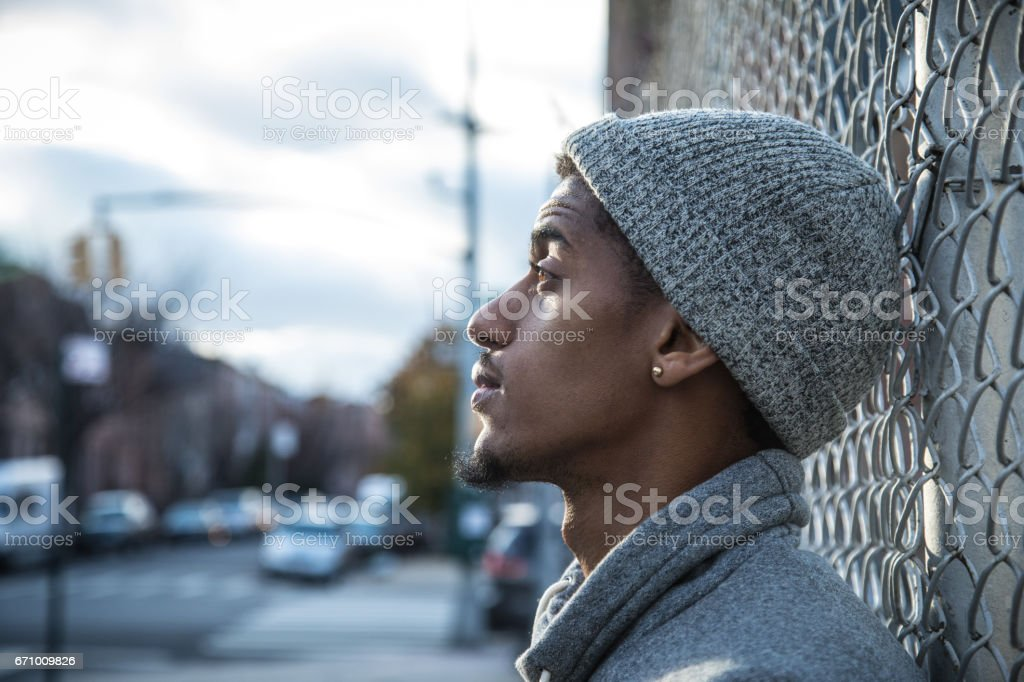 A candid portrait of a young, black man in the streets of Brooklyn, NYc at sunset stock photo