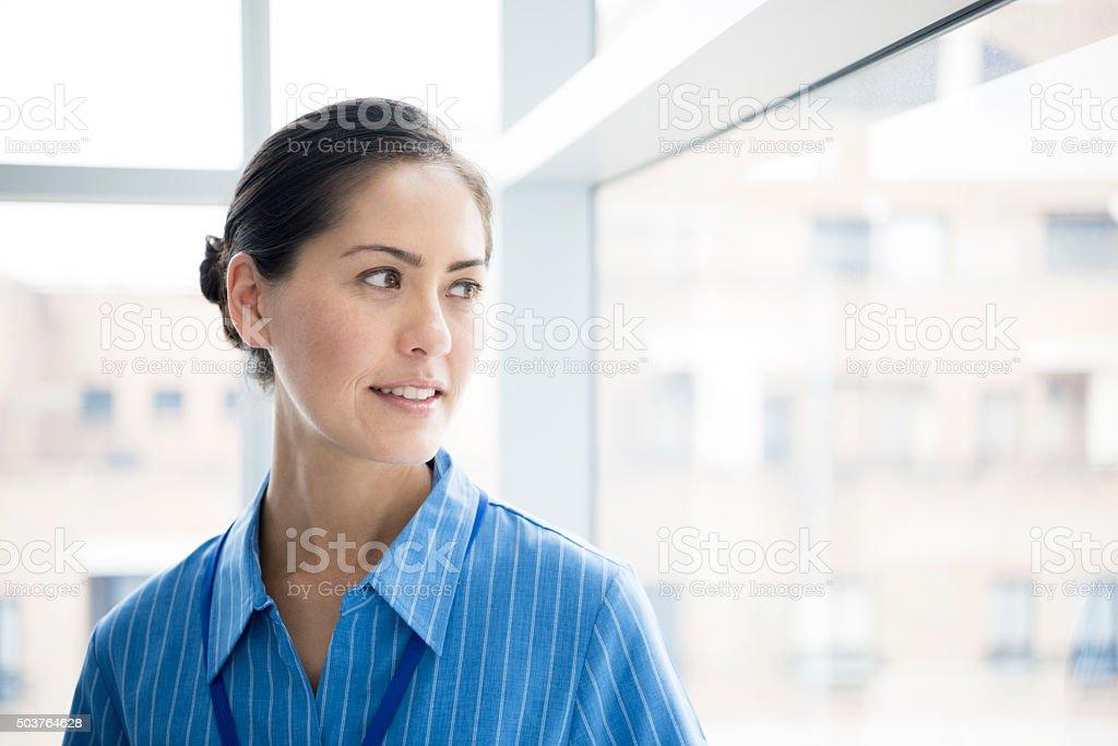 Candid portrait of Asian nurse looking through window stock photo