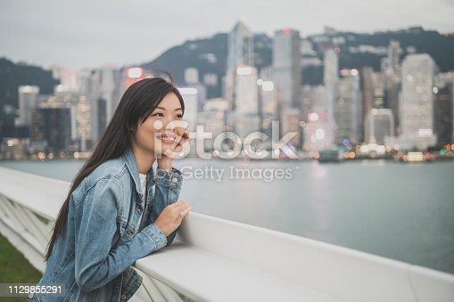 Young Chinese tourist in her 20s looking at views across the river, city in distance, smiling, sightseeing, weekend activity