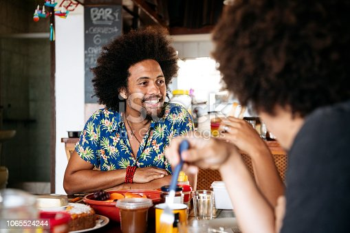 Mid adult man with Afro, relaxed and happy, looking at friends, talking during meal